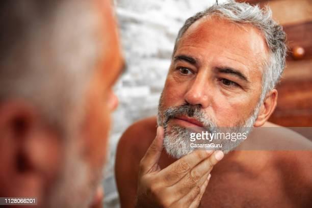 verbrande volwassen man op zoek naar de spiegel in de badkamer - kin in de hand stockfoto's en -beelden