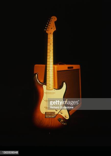 Sunburst Fender Stratocaster guitar and Fender tweed amplifier, studio shot.