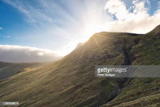 sunburst on a mountain peak; english lake district, u.k. - lens flare stock pictures, royalty-free photos & images