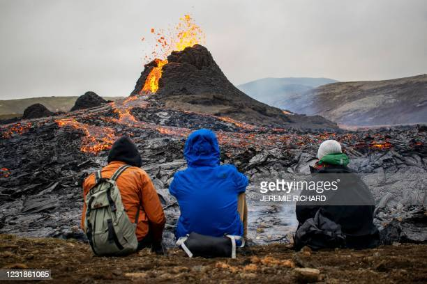 Sunday hikers look at the lava flowing from the erupting Fagradalsfjall volcano some 40 km west of the Icelandic capital Reykjavik, on March 21,...