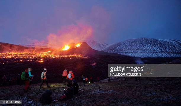 Sunday hikers visit the site of an eruption of a volcano on the Reykjanes Peninsula in Iceland on ,March 28, 2021. - A week on, big crowds of Sunday...