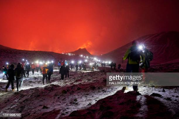 Sunday hikers walking along in the Geldingadalur valley are wearing head lights as they make their way to and from the site of an eruption of a...