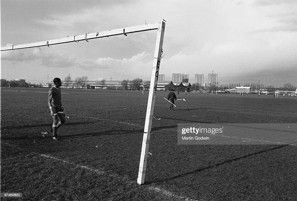 Sunday League Football, Hackney Marshes, unknown man taking the corner flags down after a match while an unknown man watches from empty net.