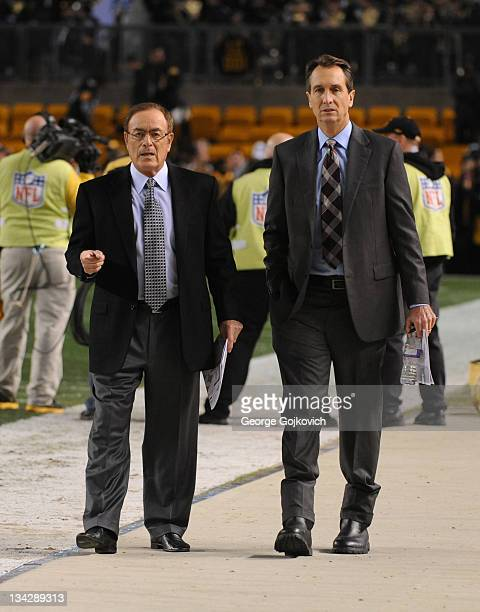 Sunday Night Football announcers Al Michaels and Cris Collinsworth walk on the sideline before a game between the Baltimore Ravens and Pittsburgh...