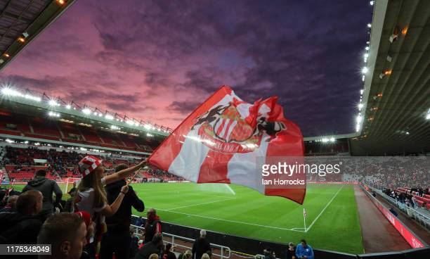 Sunderland fan waves a flag against the background of a setting sun during the Sky Bet League One match between Sunderland and Rotherham United at...