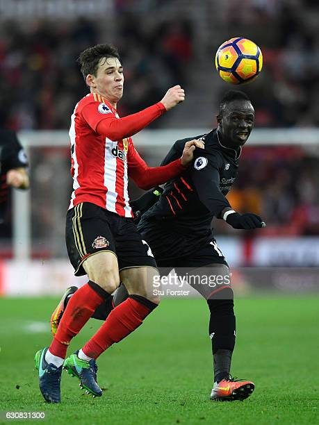 Sunderland player Donald Love is challenged by Sadio Mane of Liverpool during the Premier League match between Sunderland and Liverpool at Stadium of...