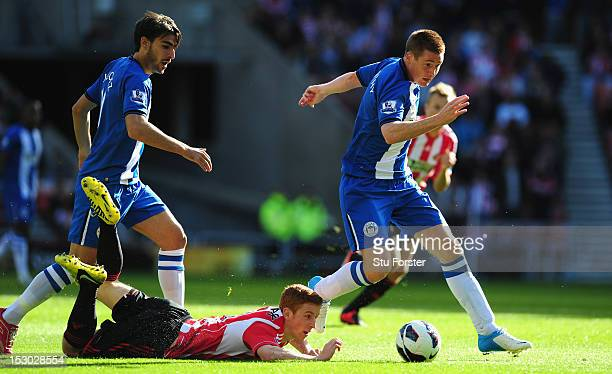 Sunderland player Jack Colback is thwarted by Wigan players Jodi Gomez and James McCarthy during the Barclays Premier League game between Sunderland...
