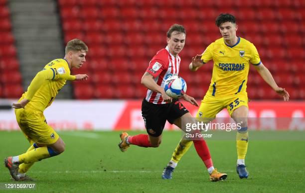 Sunderland player Jack Diamond nips through the gap between Daniel Csoka and Callum Reilly during the Sky Bet League One match between Sunderland and...