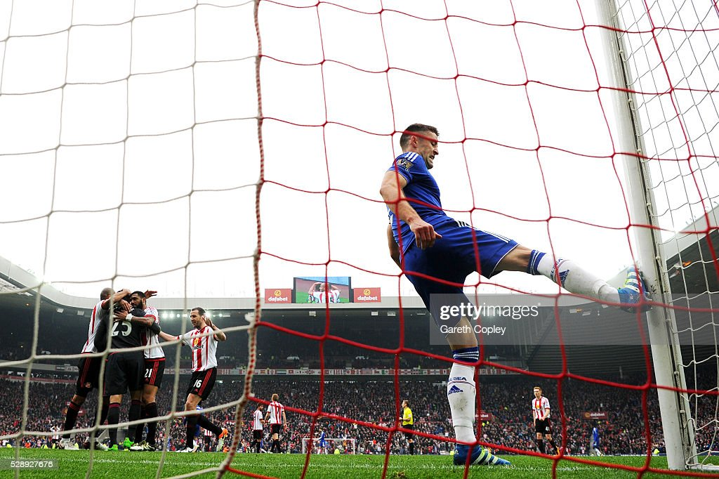 Sunderland players celebrate their 3-2 win while Gary Cahill of Chelsea kicks the post with frustration after the Barclays Premier League match between Sunderland and Chelsea at the Stadium of Light on May 7, 2016 in Sunderland, United Kingdom.