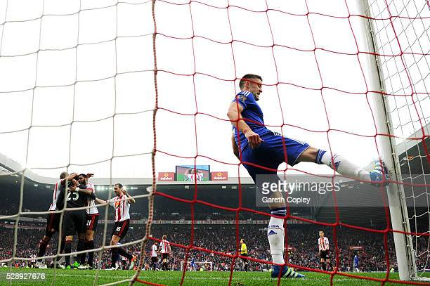 Sunderland players celebrate their 3-2 win while Gary Cahill of Chelsea kicks the post with frustration after the Barclays Premier League match...