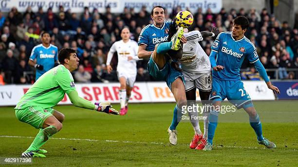Sunderland players John O' Shea and Santiago Vergini combine to challenge Bafetimbi Gomis of Swansea during the Barclays Premier League match between...