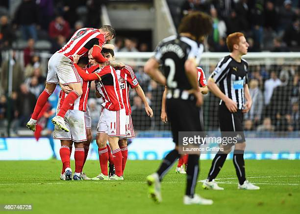 Sunderland players mob Adam Johnson of Sunderland as they celebrate victory after the Barclays Premier League match between Newcastle United and...