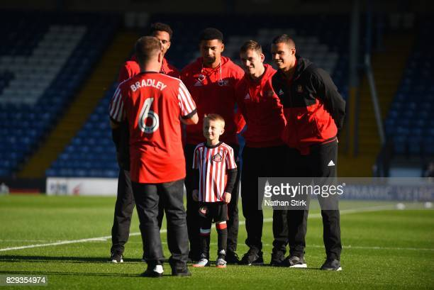 Sunderland players pose for a photograph with Bradley Lowery best friend who is the mascot during the Carabao Cup First Round match between Bury and...