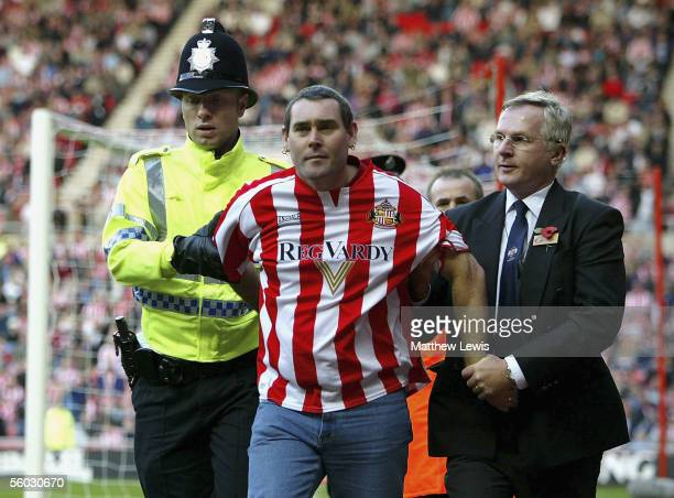 Sunderland supporter is escorted from the pitch during the Barclays Premiership match between Sunderland and Portsmouth at the Stadium of Light on...