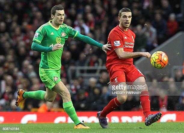 Sunderland's English midfielder Adam Johnson challenges Liverpool's English midfielder Jordan Henderson during the English Premier League football...