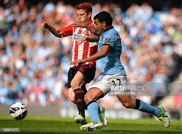 Sunderland's English midfielder Jack Colback vies with Manchester City's Argentinian striker Carlos Tevez during the English Premier League football...