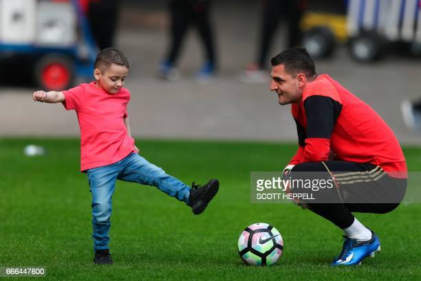 Sunderland's Italian goalkeeper Vito Mannone interacts with Bradley Lowery a fiveyearold suffering from terminal cancer ahead of the English Premier...