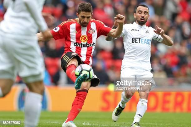 Sunderland's Italian striker Fabio Borini vies with Swansea City's English midfielder Leon Britton during the English Premier League football match...
