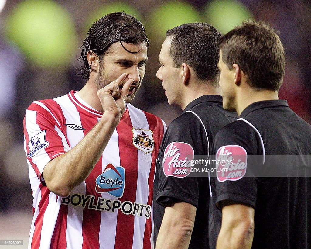 Sunderland's Lorik Cana (L) talks with the referee, Kevin Friend (C) at half-time against Aston Villa during an English FA Premier League, football match, at the Stadium of Light, Sunderland, England, on December 15, 2009. AFP PHOTO/GRAHAM STUART - FOR EDITORIAL USE ONLY Additional licence required for any commercial/promotional use or use on TV or internet (except identical online version of newspaper) of Premier League/Football League photos. Tel DataCo +44 207 2981656. Do not alter/modify photo.