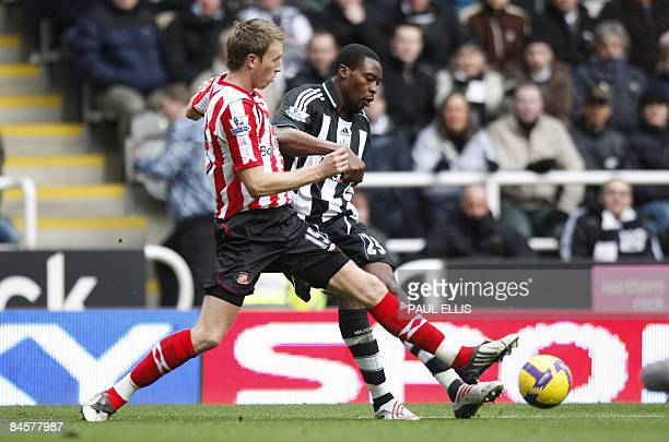 Sunderland's Welsh defender Danny Collins tackles Newcastle United's English forward Shola Ameobi during their English Premier League football match...