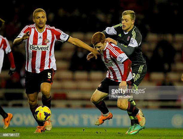 Sunderland's Wes Brown and Jack Colback in action as Stoke's John Guidetti challenges during the Barclays Premier League match between Sunderland and...