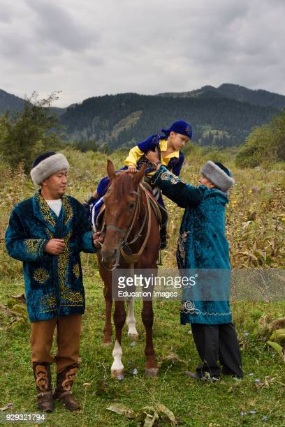 Sundet Toi circumcision with boy on horse and men in traditional Kazakh shapan coat and borik hat