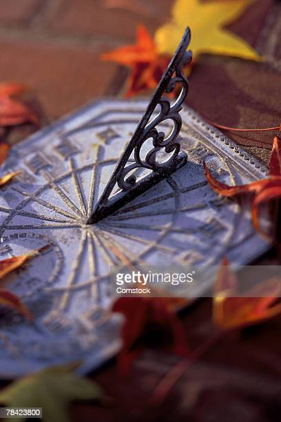 Sundial with autumn leaves