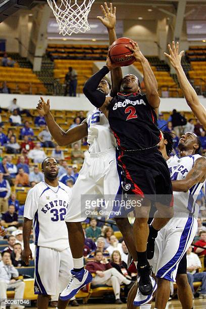 Sundiata Gaines of the University of Georgia Bulldogs makes a shot over AJ Stewart of the Univeristy of Kentucky Wildcats during the SEC Men's...