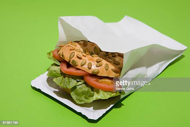 A Sunflower seed bagel sandwich with tomato and lettuce in a paper bag