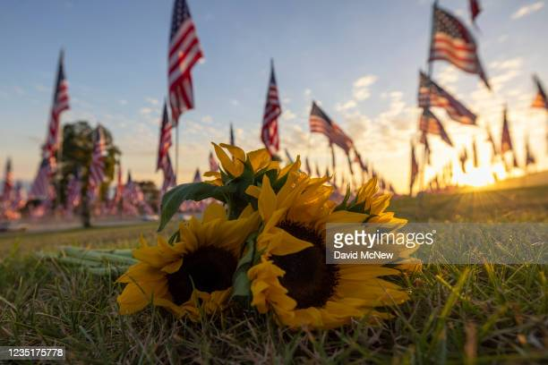 Sunflowers are laid on the ground during the 14th annual Waves of Flags on the eve of the 20th anniversary of the September 11 terror attacks in...