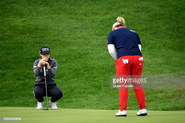 Sung Hyun Park of South Korea looks on as Ariya Jutanugarn of Thailand plays a putt during day two of the Evian Championship at Evian Resort Golf...