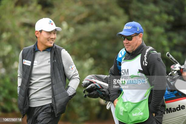 Sung Kane of South Korea and his caddie walk down the first hole fairway during the first round of The RSM Classic at the Sea Island Resort...