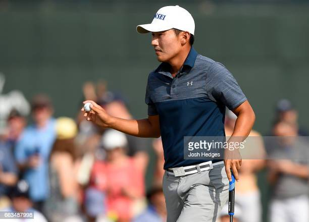 Sung Kang of South Korea acknowledges the gallery after putting on the 18th green during round three of the Shell Houston Open at the Golf Club of...