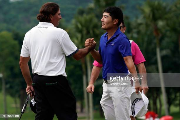 Sung Kang of South Korea congratulates Pat Perez of the United States on the 18th hole during the final round of the 2017 CIMB Classic at TPC Kuala...