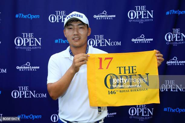 Sung Kang of South Korea holds a hole flag after qualifying for the Open Championship during the fourth and final round of the Quicken Loans National...