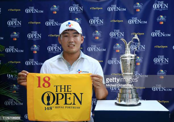 Sung Kang of the United States poses with the Claret Jug while holding a hole flag after qualifying for the Open Championship during The Open...