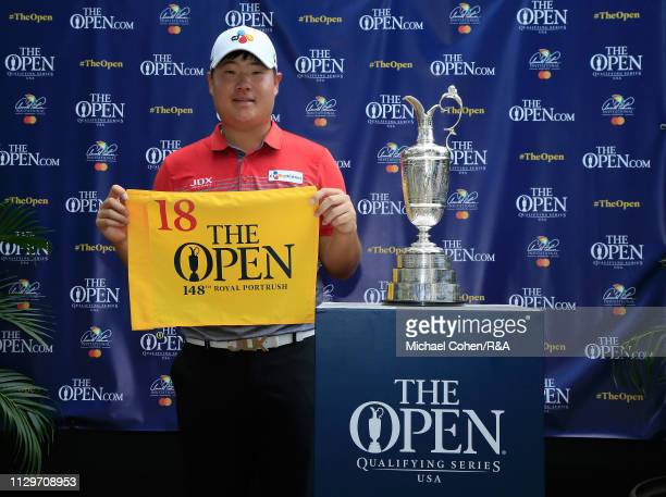 Sungjae Im of South Korea poses with the Claret Jug while holding a hole flag after qualifying for the Open Championship during The Open Qualifying...