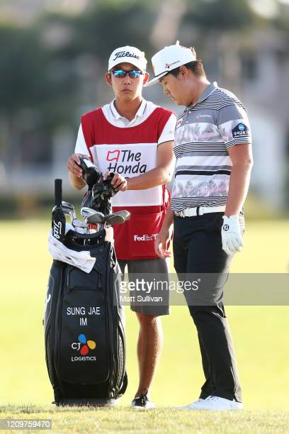 Sungjae Im of South Korea pulls a club from his bag on the 18th hole during the Honda Classic at PGA National Resort and Spa Champion course on March...