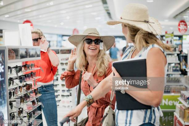 sunglasses fun in duty free - airport terminal stock photos and pictures