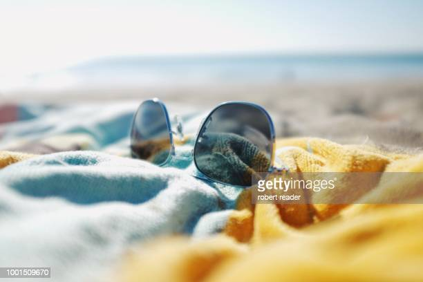 sunglasses on beach towel - sunglasses stock pictures, royalty-free photos & images