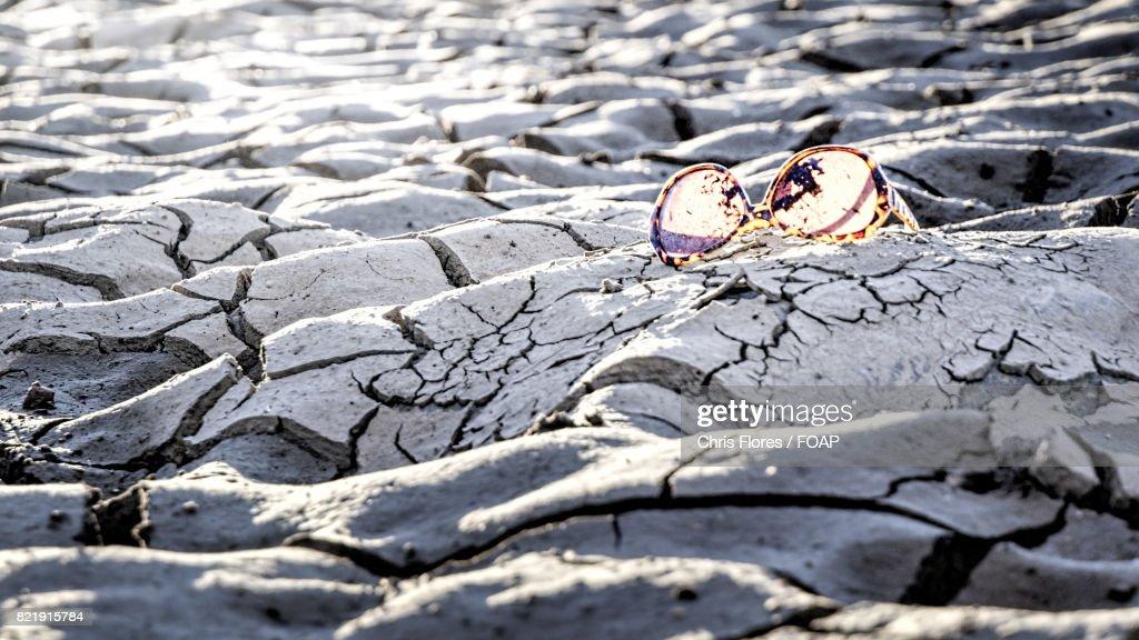 Sunglasses on mud : Stock Photo