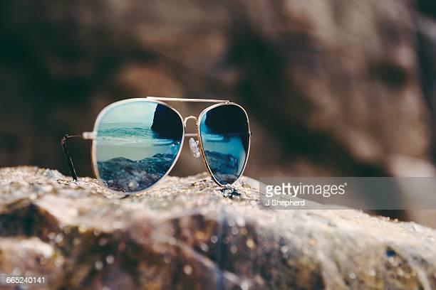 Sunglasses reflecting the shoreline.