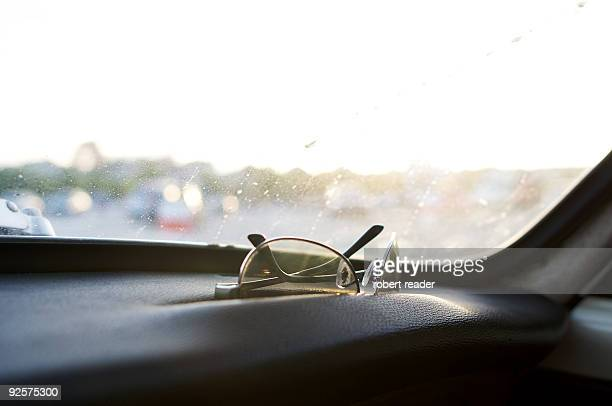 Sunglasses sitting on car dashboard