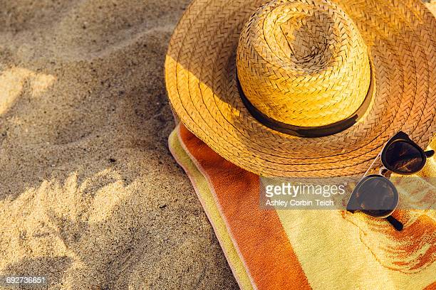 Sunglasses, straw hat and beach towel on sand