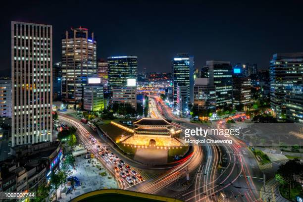 sungnyemun gate (namdaemun market) or namdaemun gate with light trails of car at night in seoul, south korea. - korea stock pictures, royalty-free photos & images