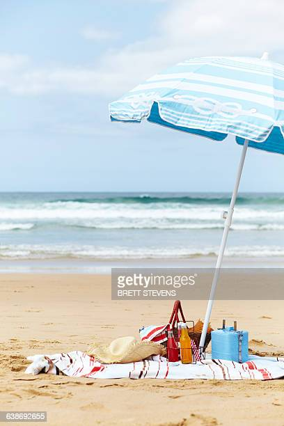 sunhat, cool box and picnic basket on beach towel underneath parasol on beach - esky stock photos and pictures