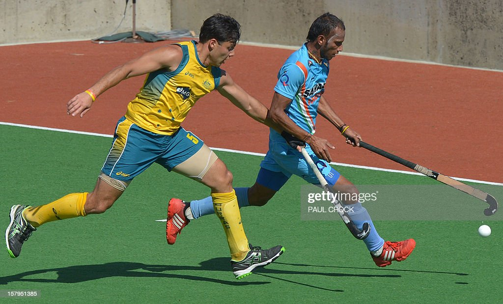 Sunil Sv of India (R) fights off a challenge by Chris Ciriello of Austalia (L) during the second semifinal at the men's Hockey Champions Trophy tournament in Melbourne on December 8, 2012. IMAGE STRICTLY RESTRICTED TO EDITORIAL USE - STRICTLY NO COMMERCIAL USE AFP PHOTO / Paul CROCK