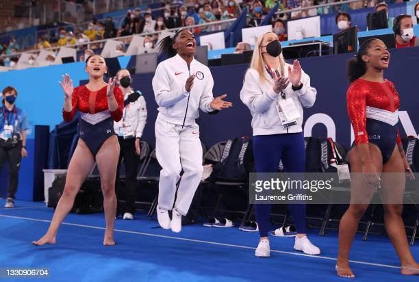 Sunisa Lee, Simone Biles, coach Cecile Landi and Jordan Chiles of Team United States cheer as Grace McCallum competes in floor routine during the...