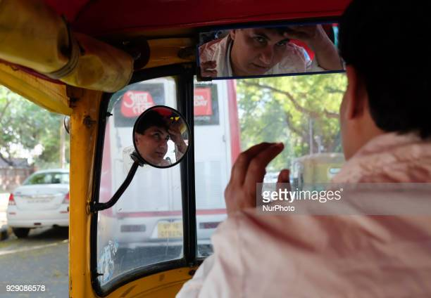 Sunita Choudhary 40 North India's first autorickshaw driver fixes her hair looking into her autorickshaw's mirror on 6th March 2018 in New Delhi...