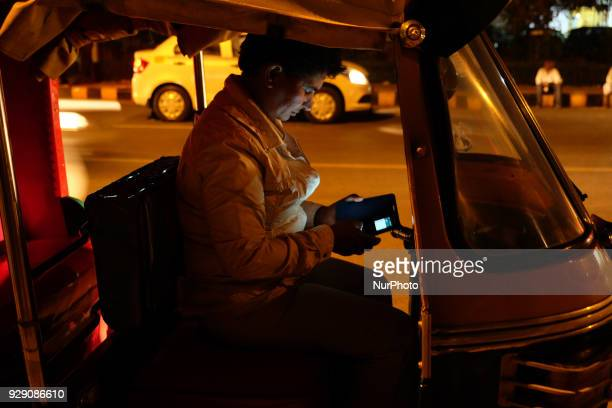 Sunita Choudhary North India's first autorickshaw driver checks her phone while waiting for customers in Central Delhi on 6th March 2018 Sunita...